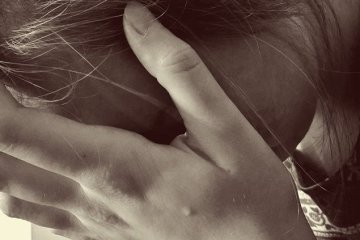 Image shows a woman holding her head.