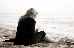 Image shows a woman reading on a beach.