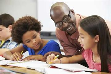 Image shows a teacher and students.