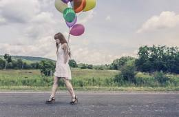 Image shows a woman walking and holding balloons.