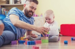 Image shows a dad playing blocks with a small baby.