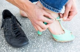 Image shows a woman swapping between heals and walking shoes.