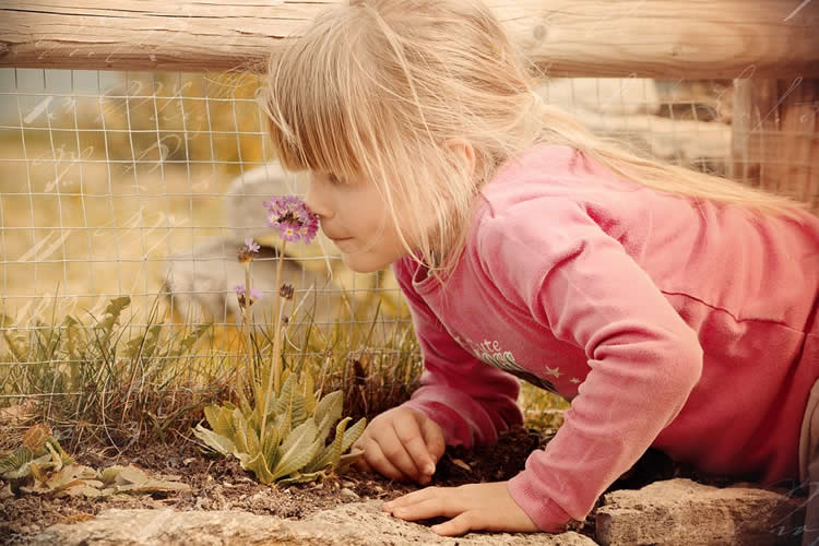 Image shows a girl sniffing a flower.