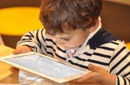 Image shows a child with a tablet.