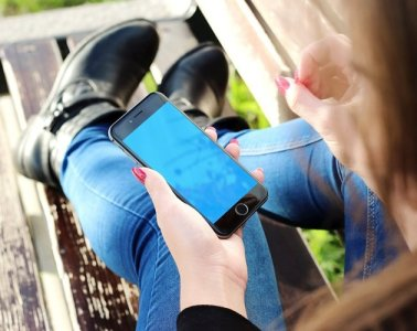 Image shows a woman playing with a smartphone.