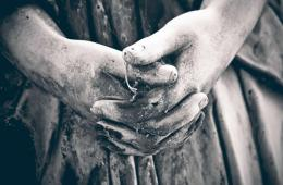 Image shows a tomb angel's hands.