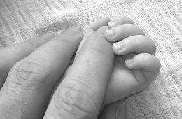 Image shows a man holding a baby's hand.