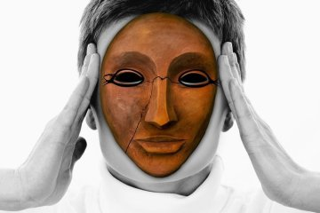 Image shows woman holding her head and wearing a mask.