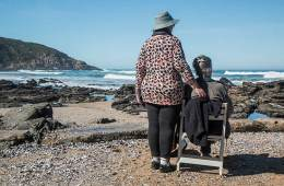 Image shows old people on a beach.