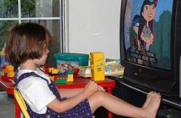 Image shows a kid watching TV.