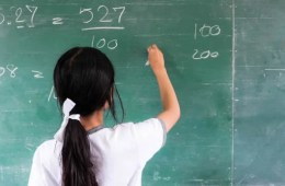 Image shows a child writing math equations.