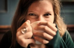 Image shows a woman drinking coffee.