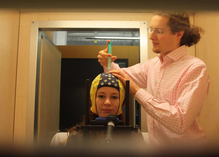 Image shows a woman in an EEG cap.