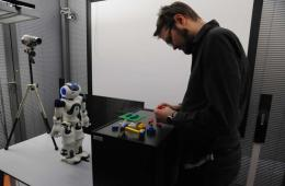 Image shows a person and robot.