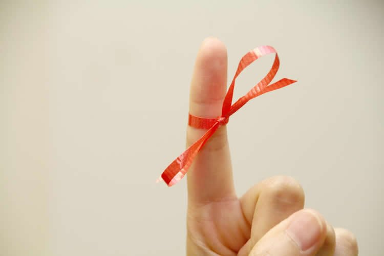 Image shows a finger with a bow tied on it.