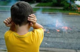 Image shows a child covering their ears.
