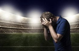 This image shows a person crying at a football stadium.