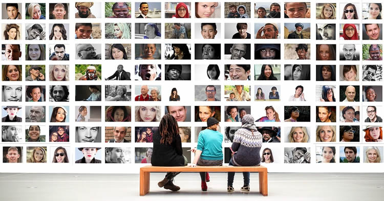Image shows people looking at a wall of photos.