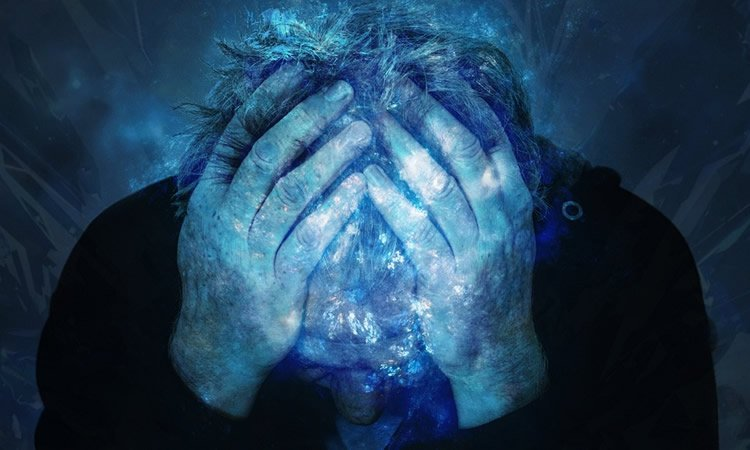 Image shows a man holding his head.
