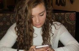 Image shows a teen using a smartphone.