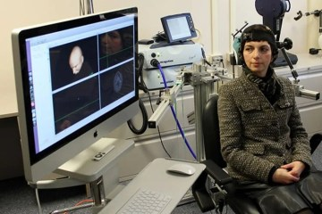 Image shows a lady sitting next to a monitor undergoing rTMS.