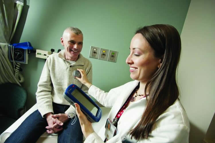 Image shows a doctor and patient with Parkinson's.
