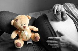 Image shows a pregnat woman and a teddy bear.
