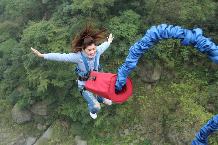 Image shows a woman bungee jumping.