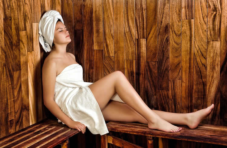 Image shows a woman in a sauna.