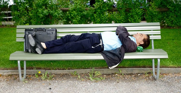 a man sleeping on a park bench
