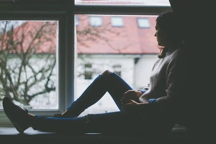 a woman sitting by a window