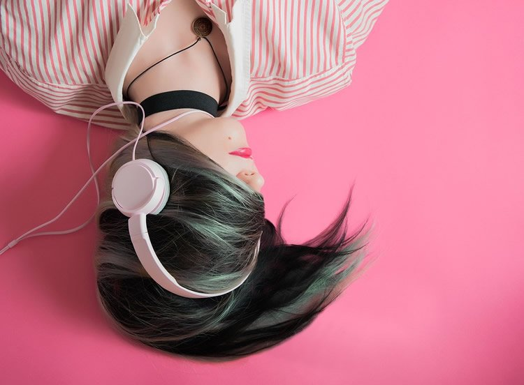 Image shows a woman listening to music.