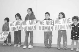 kids holding we are human signs
