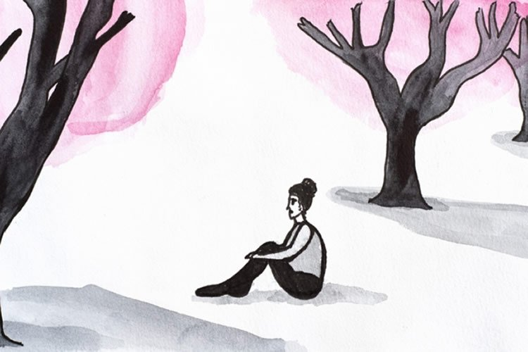 a woman sitting under trees