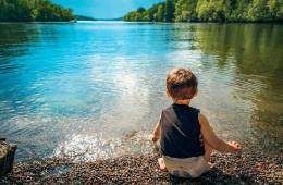 This shows a child sitting by a beautiful lake