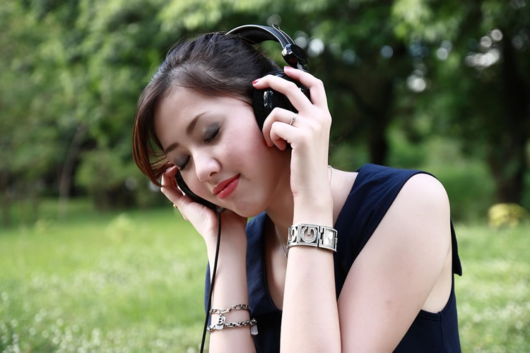 This shows a woman listening on headphones