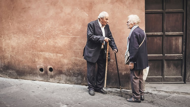 This shows an older man and woman talking on a street