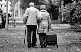 This image shows an old couple walking down a street.