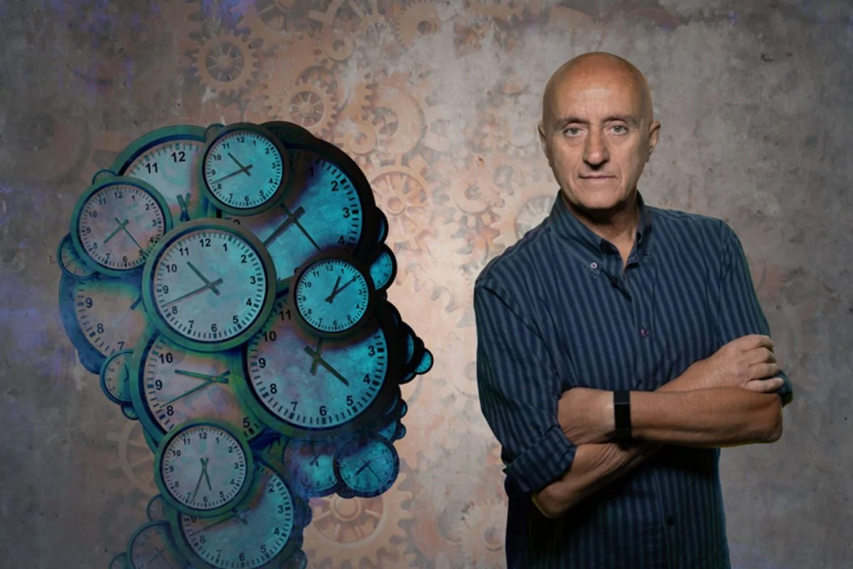 This shows the researcher next to a head made of clocks