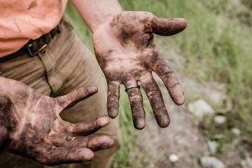 This shows a man with dirty hands