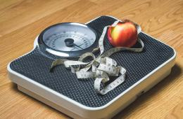 This shows a weighing scale, a tape measure and an apple