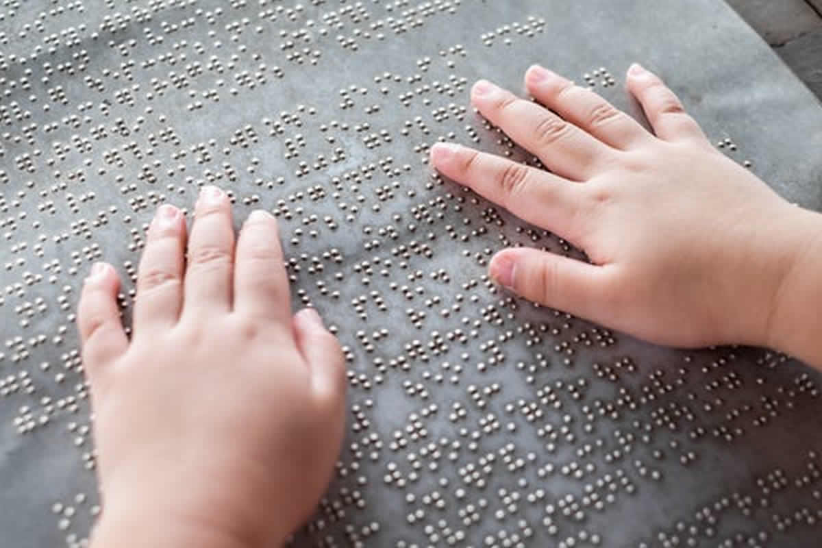 This shows a person reading braille with their fingers