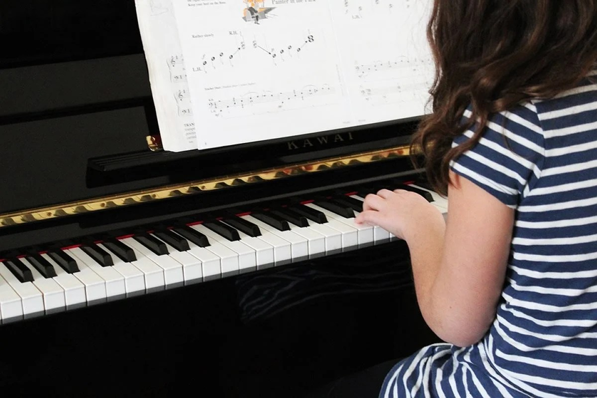 This shows a little girl playing the piano