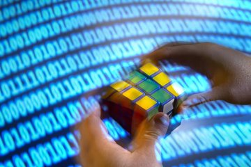 This shows a binary screen and a person solving the rubiks cube