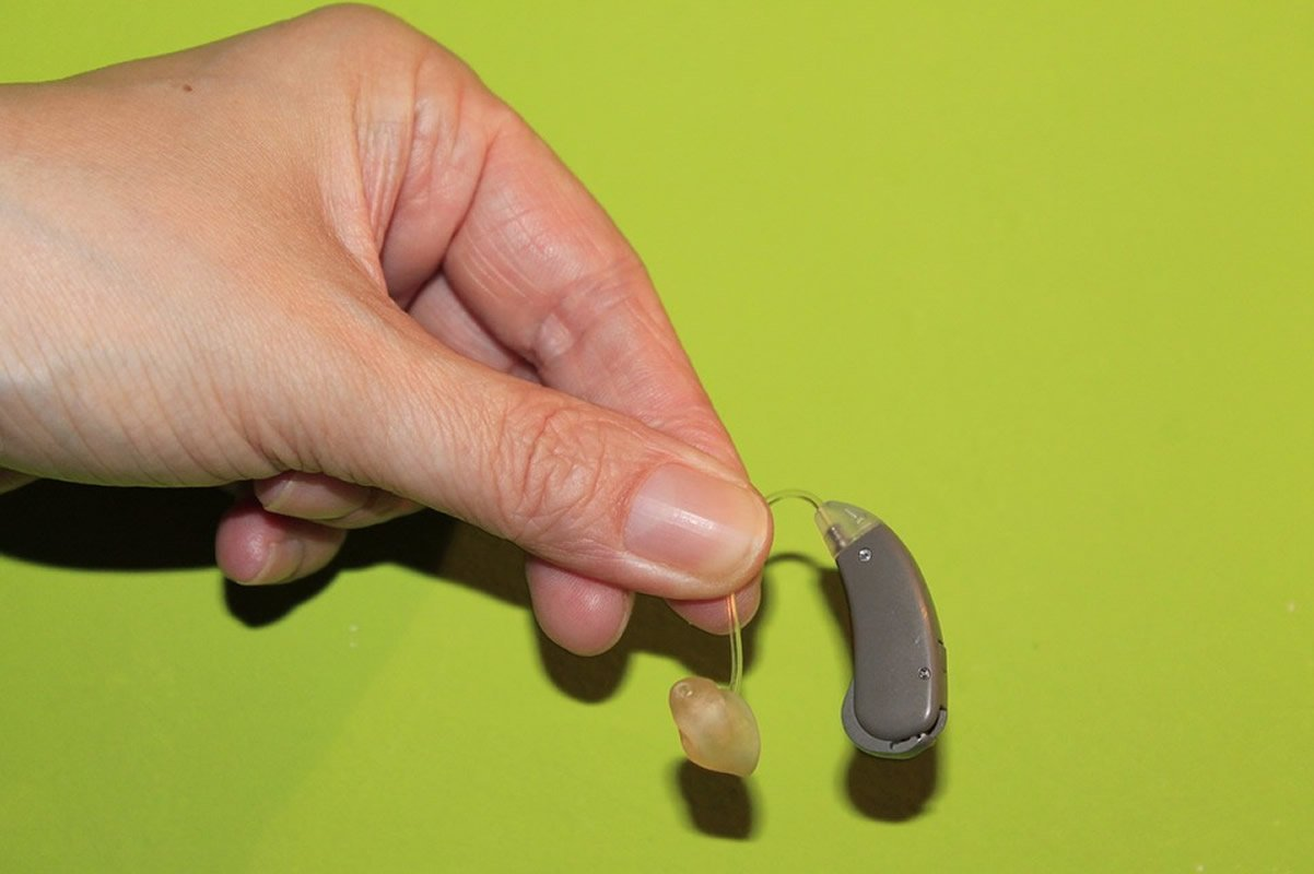 This shows a person holding a hearing aid in their fingers