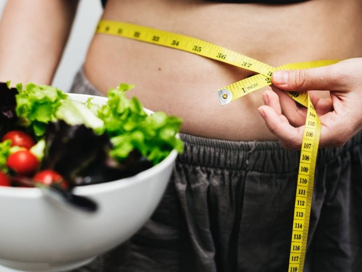 This shows a woman next to a bowl of salad measuring her tummy