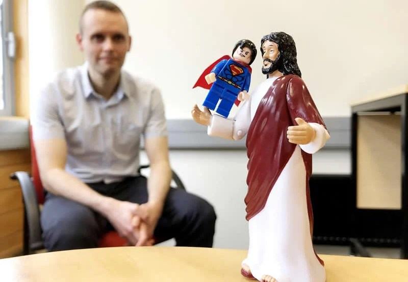 This shows a statue of jesus holding up a lego superman