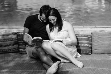 This shows a happy couple reading by a lake