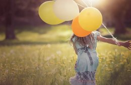 This shows a little girl running with balloons