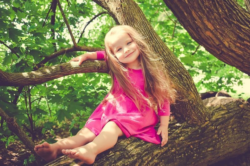 This shows a happy girl in a tree